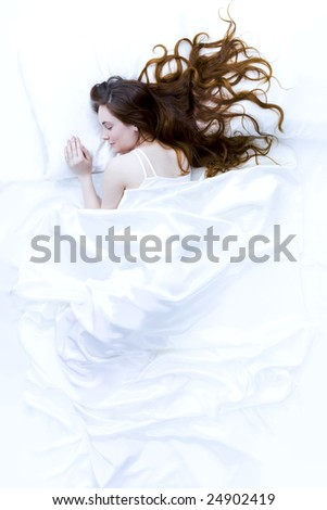 Above view of young beautiful woman sleeping in bed covered with white silky sheet
