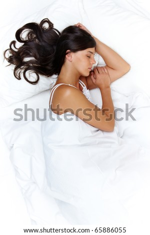 Above view of young beautiful woman sleeping in bed covered with white silky sheet - stock photo