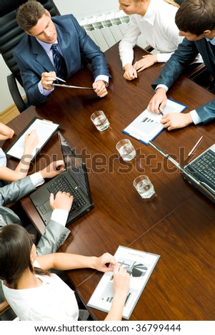 Above view of young co-workers interacting with each other at meeting - stock photo