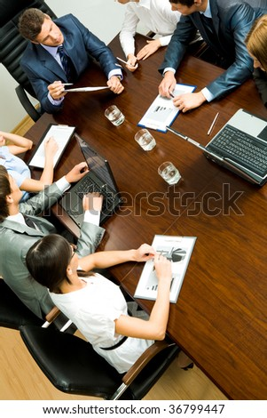 Above view of young co-workers planning work at meeting - stock photo