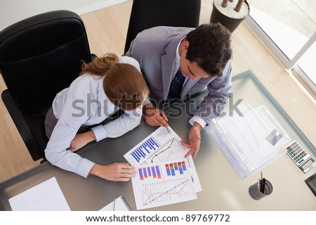 Above view of young consultant analyzing data with her client - stock photo