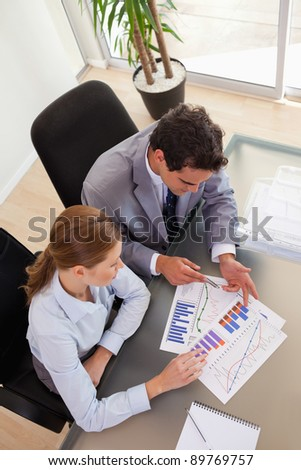 Above view of young consultant analyzing diagram with her client - stock photo