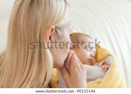 Above view of young mother kissing her baby's hand - stock photo