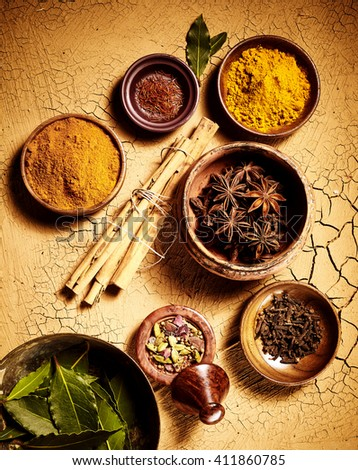 Above view on pots of assorted whole leaf and ground herbs and spices used for Indian cuisine over cracked painted brown surface - stock photo