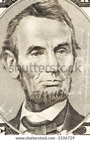 Abraham Lincoln's portrait on front of a five dollar bill. - stock photo