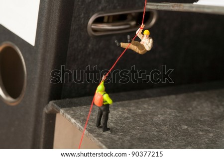 Abseiling On Office Files, miniature models of mountaineers abseiling down off an office file. - stock photo