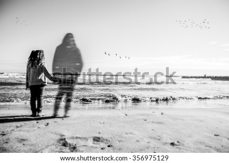 Absence: A girl holds the hand what appears to be the spirit of his dead mother. The image has been selectively blurred to give a touch of mystery. Can see some birds in the horizon. - stock photo