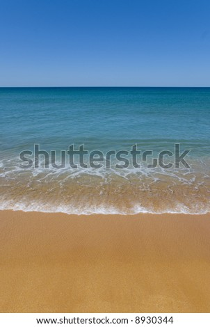 absolute perfect beach with golden sand. a gentle wave onto shore with beautiful foam patterns. The shallow water is aqua to the deep blue of the ocean. Perfect Blue Sky and beach for copyspace