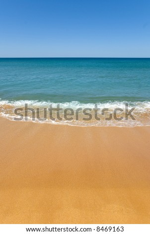 absolute perfect beach with golden sand. a gentle wave washes onto shore. The shallow water is turquoise aqua to the deep blue of the ocean. Perfect Blue Sky and beach for copyspace