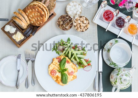 Absolutely Amazing Top View of Bread, Tea, Tasty Berry Jam, Scrambled Eggs with Salad on the Table for Breakfast, Brunch Time in Restaurant, Breakfast Conception, Traditional English Tea Ceremony - stock photo