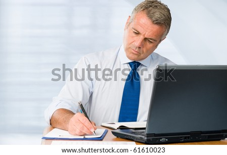 Absorbed mature businessman working and taking notes in his modern office - stock photo