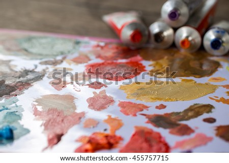 Abstract acrylic paint, paint tubes and brushes on white wooden palette - stock photo