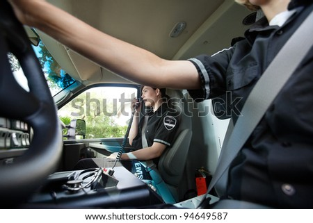 Abstract ambulance interior with female paramedic talking on radio with dispatcher