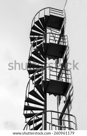 Abstract architecture fragment, old outdoor metal spiral ladder on the wall, black and white photo - stock photo