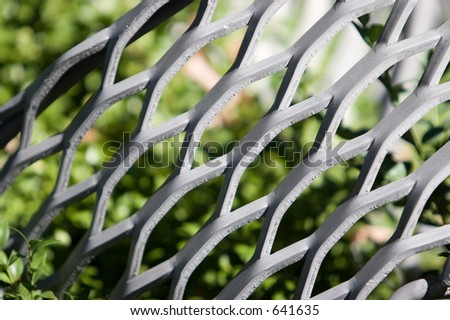 Abstract Art: Metal vs Photosynthesis.  Great perspective between the cold death of hard metal and warmth of life from green leaves.