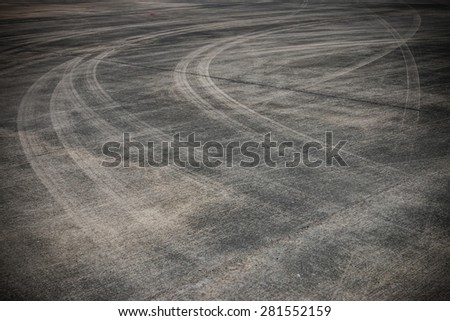 Abstract asphalt road background with crossing of tires tracks.