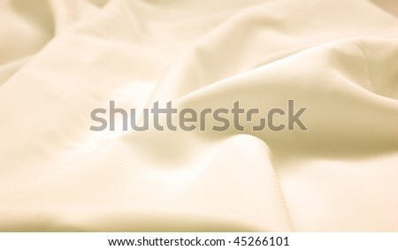 Abstract background beige silk fabric with waves. Shallow DOF