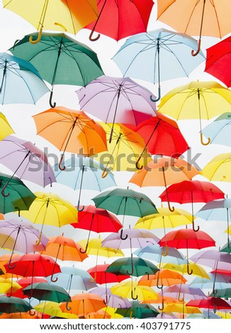 Abstract background. Bright colorful hundreds of umbrellas floating above the street - stock photo
