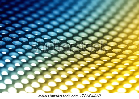 Abstract background: Colorful perforated bent metal sheet grid. - stock photo