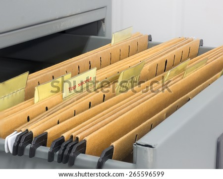 Abstract background image of colorful hanging file folders in drawer with top secret stamp . Macro with with extremely shallow dof. Selective focus in front edges of files. - stock photo