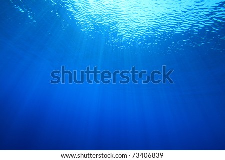Abstract background image of sun rays in blue water - stock photo