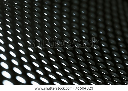 Abstract background image: Perforated bent metal sheet grid in black and white. - stock photo