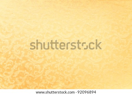 Abstract background of a heavy golden brocade fabric with interwoven repeat design. - stock photo