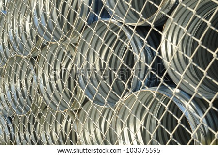 Abstract background of galvanized metal culverts behind chain link fence - stock photo