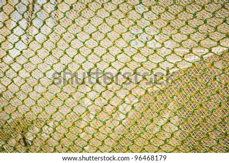 Abstract background of openframe knotted yellow green netting used by trawlers as a fishing net when deep sea fishing - stock photo