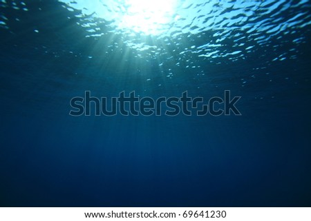 Abstract background of sunbeams in blue water - stock photo