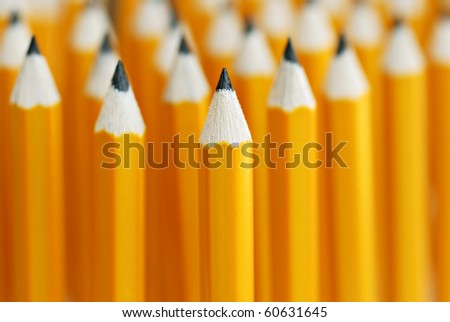 Abstract background of yellow pencils with extremely shallow dof.  Selective focus limited to front pencil. - stock photo
