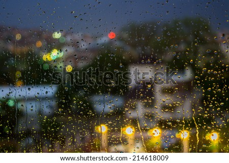 abstract background raindrops on glass on background of blurred warm  with cool blue and purple lights with bokeh effect - stock photo