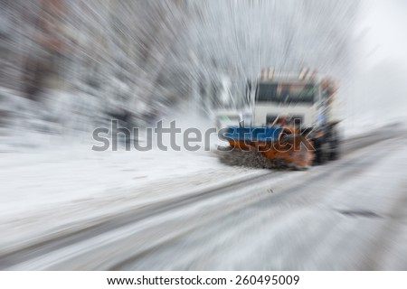 Abstract background -   snow plough cleaning the streets covered in snow and mud during heavy snowfall  - radial zoom blur effect defocusing filter applied - stock photo