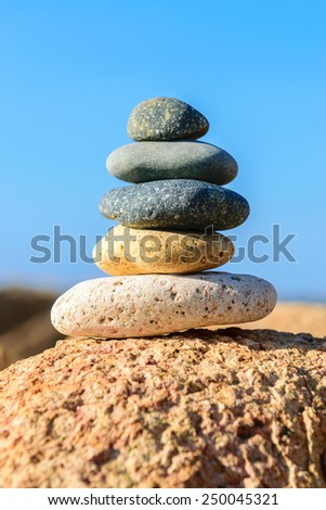 Abstract background. Stone tower on a pebble beach again blue sky - stock photo