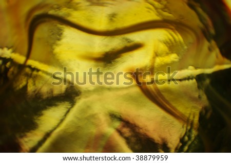 abstract background wallpaper of light refracted through yellow swirled glass - stock photo