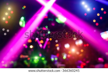 Abstract background with defocused bokeh of laser show in modern disco party night club - Concept of nightlife with music and entertainment - Image with powered colored halos and vivid bright lights  - stock photo