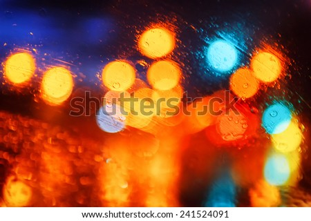 Abstract background with multicolor city lights through wet window - stock photo