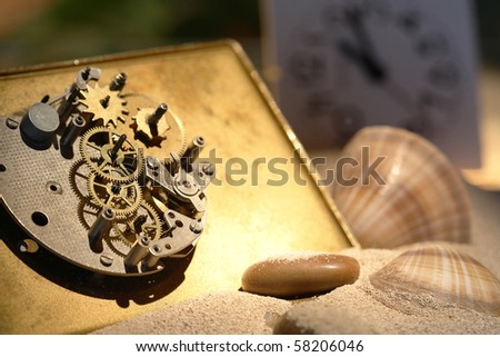 Abstract background with old clock mechanism standing on sand with stones and shells