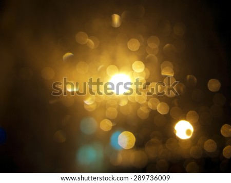 abstract black background, gold bubble lights or snowflakes falling at night. Bokeh Christmas background with circle designs or blurred stars shining, glitter magic background - stock photo