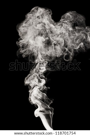 Abstract black smoke swirls over the black background