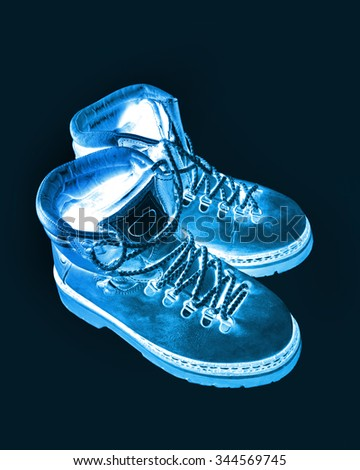 Abstract blue image of old boots on black - stock photo