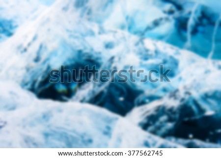 Abstract Blue river ice with large cracks. Deep blur.