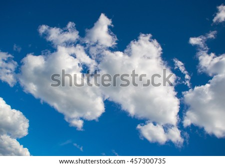 abstract blue sky and fluffy white clouds in the daytime - stock photo