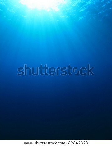 Abstract blue water background of sunbeams in the ocean - stock photo
