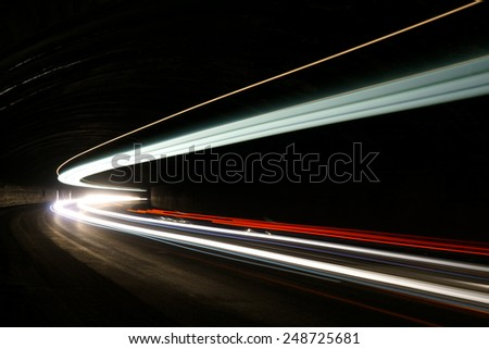 Abstract blue, yellow, white and red rays of light in a car tunnel - stock photo