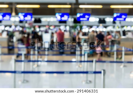 Abstract Blur Background : Airport Check-In Counters With Passengers And Crowd Control Barriers With Bokeh - stock photo