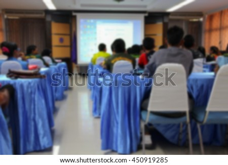 abstract Blur blurred Student sitting in classroom with teacher front and projector slide screen