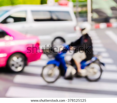 abstract blur car and young man riding motorcycle at the pedestrian zebra traffic walk way in the city. - stock photo
