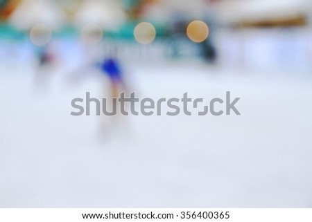 Abstract blur image of ice skater on skating rink. - stock photo