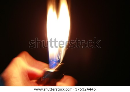 abstract blur Motion Hand with lighter igniting sparks on dark background - stock photo